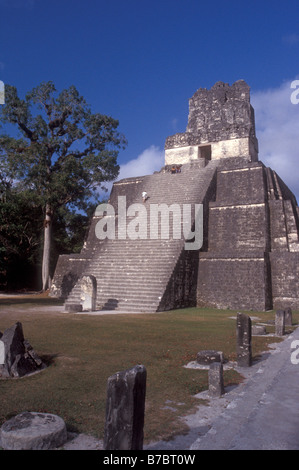 Tourist climbing Temple II or Temple of the Masks at the Mayan ruins of Tikal in Tikal National Park, El Peten, - Stock Photo