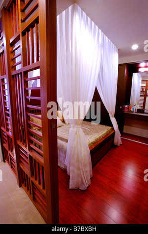 Four poster bed white curtains tied up - Stock Photo