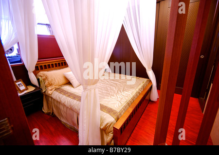 Four poster bed with white curtains tied up at four corners in a bedroom - Stock Photo