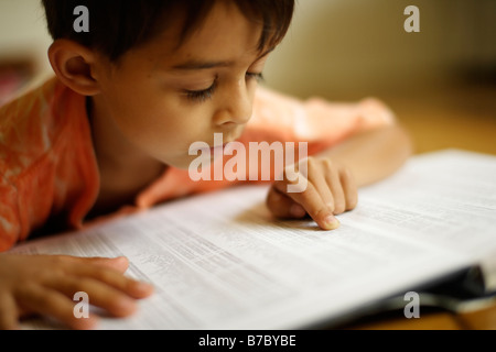 Six year old boy points to index of atlas - Stock Photo