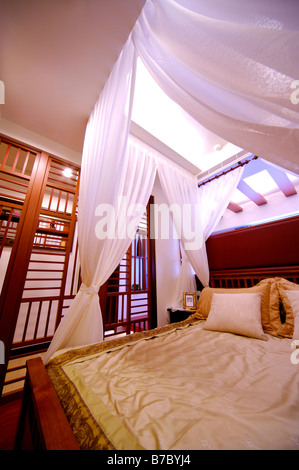 Four poster bed with white curtains - Stock Photo