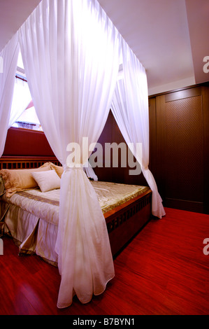 Four poster bed with white curtains tied up at the corners in the bedroom - Stock Photo