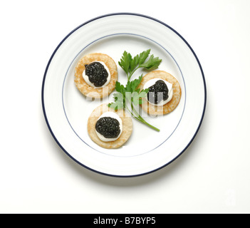 Three crackers with black caviar, green garnish on a round white dinner plate - Stock Photo