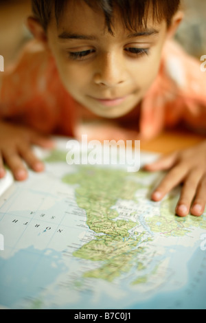 Six year old boy looks in atlas at map of UK - Stock Photo