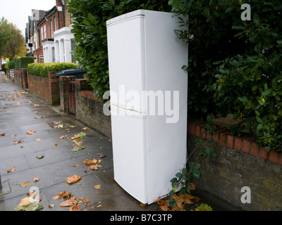 Discarded fridge freezer on pavement outside house London England UK - Stock Photo