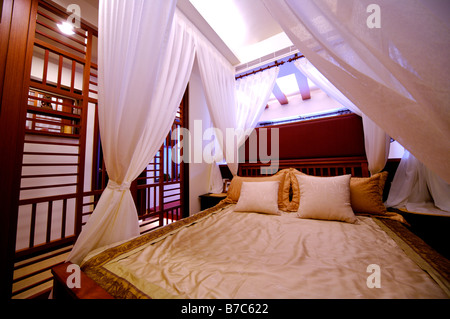 Modern four poster bed with white curtains at the four corners - Stock Photo