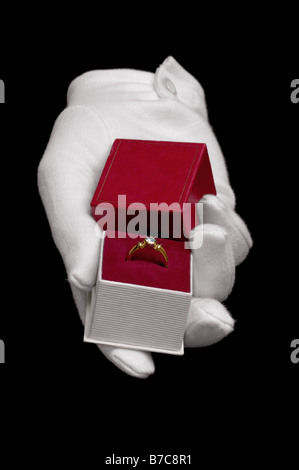 Hand wearing a white glove presenting a diamond ring in a proposal of marriage Isolated on a black background - Stock Photo