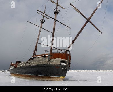 Rusting grounded ship in frozen water - Stock Photo