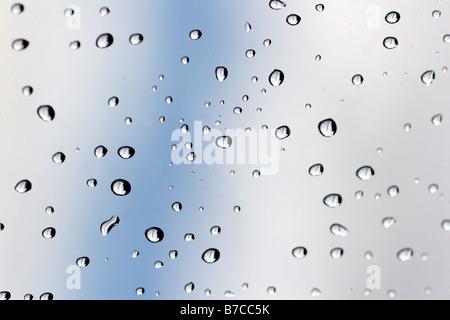 Rain drops on window against sky - Stock Photo