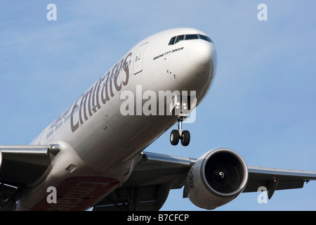 close up of Emirates airline Boeing 777 300 on final approach to land - Stock Photo