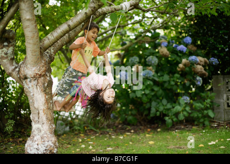 Brother and sister on swing together aged six and five years - Stock Photo
