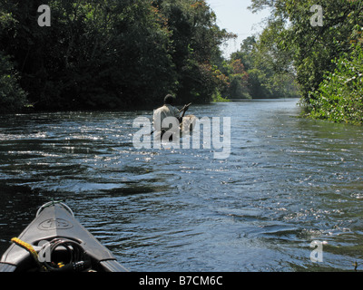 Prow of Canadian canoe following local fisherman in dugout canoe through jungle channel on Luvua River in Katanga - Stock Photo