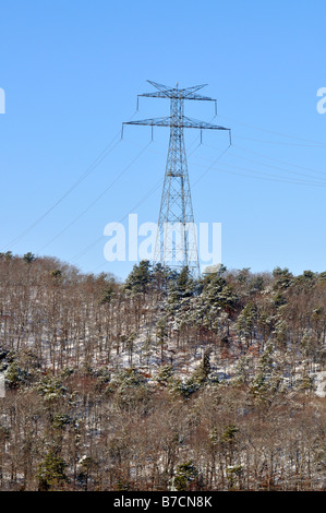 Tower for high tension power lines in winter with snow evergreen trees and blue sky - Stock Photo