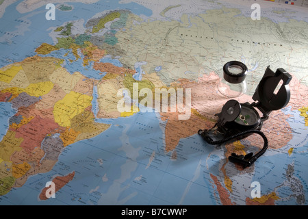 World map showing africa, europe and asia with military compass and magnifying glass - Stock Photo