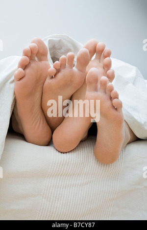 A couple's feet lying in bed - Stock Photo