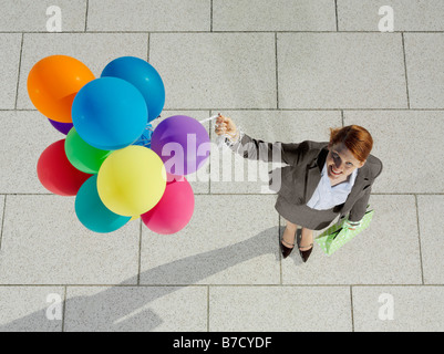 A young woman holding a bunch of balloons - Stock Photo