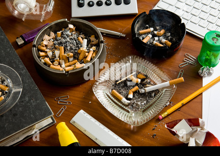 An office desk cluttered with office supplies and ashtrays - Stock Photo