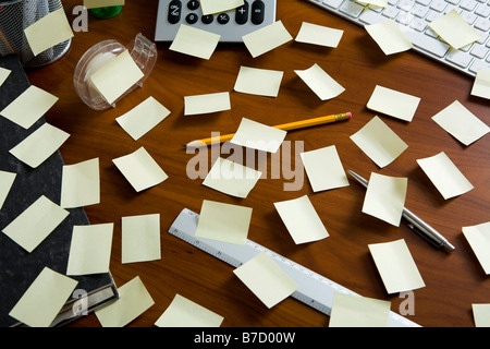 An office desk cluttered with adhesive notes and office supplies - Stock Photo