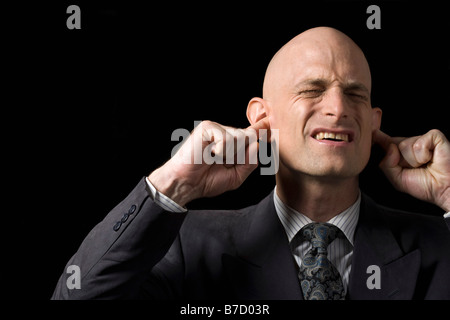 A man blocking his ears with his fingers - Stock Photo