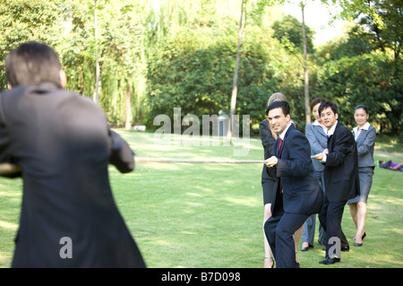 Six business people pulling a rope on the lawn - Stock Photo