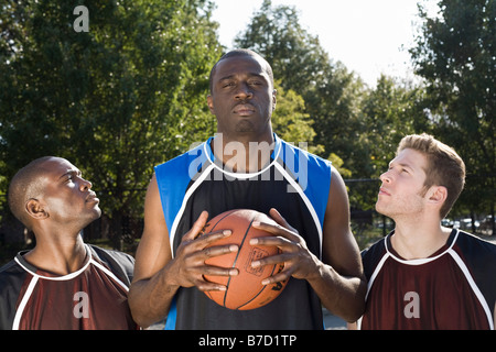 Three basketball players, in a row - Stock Photo