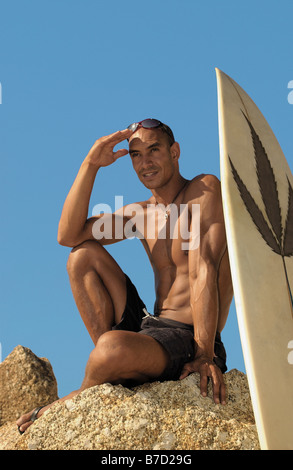 A man sitting on a rock next to a surfboard - Stock Photo