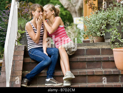 Young girls telling each other secrets - Stock Photo