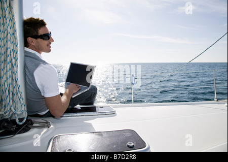 Rear view of a man using a laptop on a yacht - Stock Photo