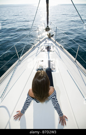 A woman sitting on the bow of a yacht - Stock Photo
