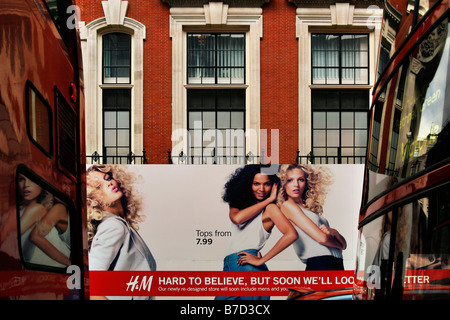 Two buses pass by an H&M / Hennes store on London's Oxford Street - Stock Photo