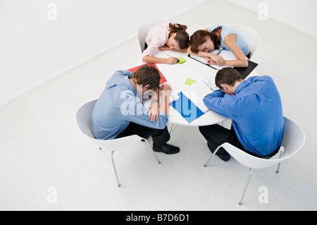 Colleagues asleep on an office table. - Stock Photo