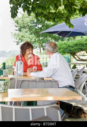 Man and woman talking over drinks - Stock Photo
