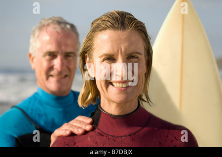 Couple wearing wetsuits on a beach - Stock Photo