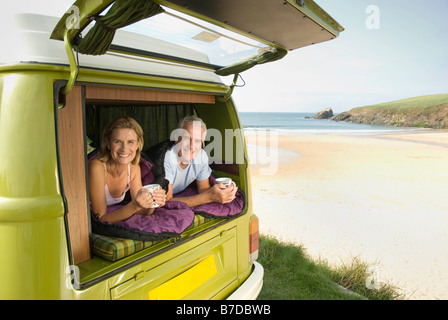 Mature couple lying in camper van - Stock Photo