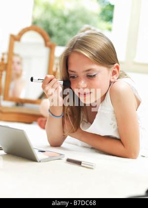 Girl putting on make-up - Stock Photo