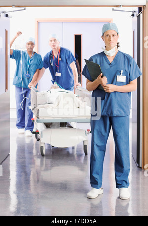 Three doctors pushing a patient in bed - Stock Photo