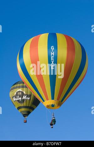Pilot in a cloudhopper balloon and an oir 17A hot air balloon fling in a bright blue sky