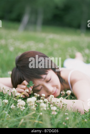Young woman lying in field - Stock Photo