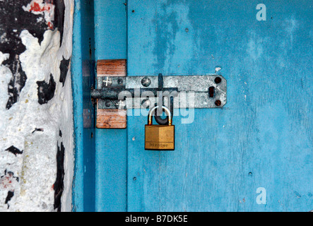 a bolted and padlocked old door. - Stock Photo