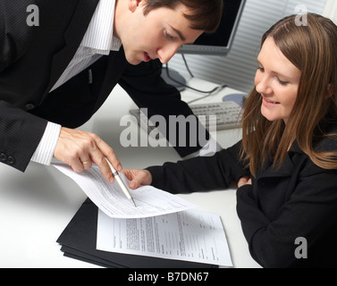 Two contemporary business people discussing a document - Stock Photo