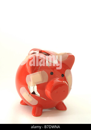 A BROKEN RED PIGGYBANK HELD TOGETHER WITH PLASTERS. - Stock Photo