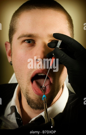 Portrait of a man about to get his tongue pierced - Stock Photo
