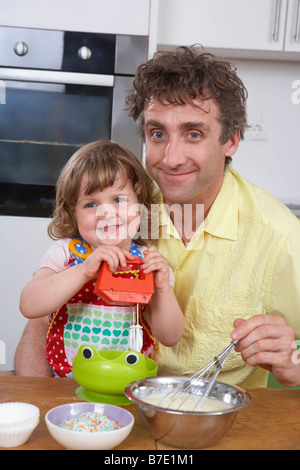 Father and daughter, stirring batter - Stock Photo