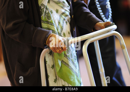An elderly Sikh lady is helped to her chair in a multicultural extra Care home Bradford West Yorkshire