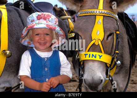 A little girl in a sunhat is smiling beside 'Tiny' a seaside donkey on the sandy beach of Skegness Lincs UK Sara - Stock Photo