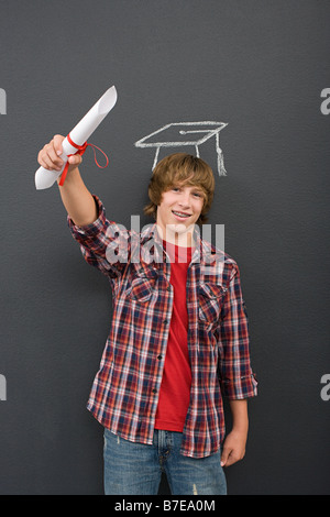 A boy holding a scroll and a chalk mortar board - Stock Photo