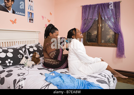Mother combing her daughters hair - Stock Photo