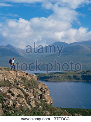 A WALKER TAKES IN THE VIEW OVER LOCH NA KEAL WITH A VIEW TO BEN MORE ISLE OF MULL INNER HEBRIDES - Stock Photo