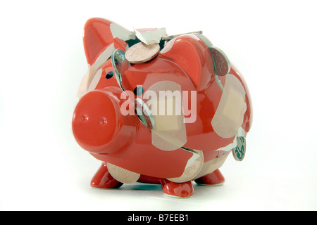 A BROKEN RED PIGGYBANK LOSING ITS CONTENTS OF BRITISH COINS... HELD TOGETHER WITH PLASTERS. - Stock Photo
