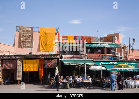 Marrakech Morocco Berber carpets hanging outside a shop with people dining out in pavement cafe in Place Jemma el - Stock Photo